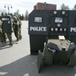 SWAT-Police-stand-next-to-a-SWAT-robot-in-Sanford-Maine-during-a-media-demonstration.-AP-Photo-by-Robert-F.-Bukaty-e1408286540949